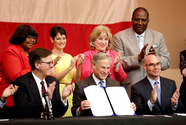 Gov. Greg Abbott holds up House Bill 3, the school finance bill, after signing it into law Tuesday.