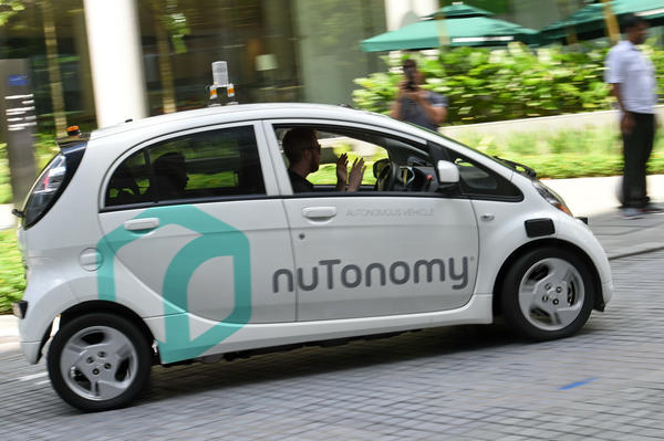 A driver sits in a moving driverless car during a 2016 public trial run in Singapore.