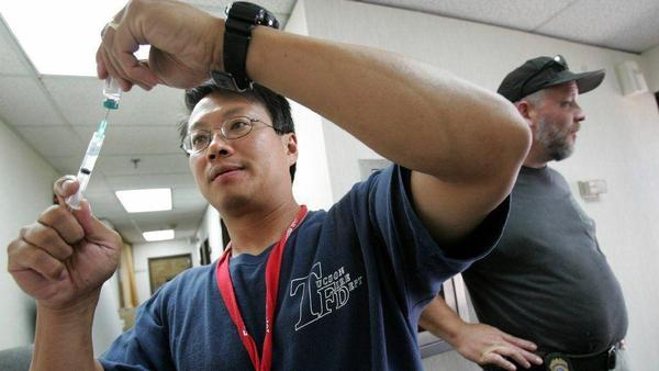 Andy Yeoh of National Disaster Medical System in Tuscon prepares an immunization shot for Hepatitis A at a medical camp in Chalmette, La., that was heavily damaged by Hurricane Katrina.