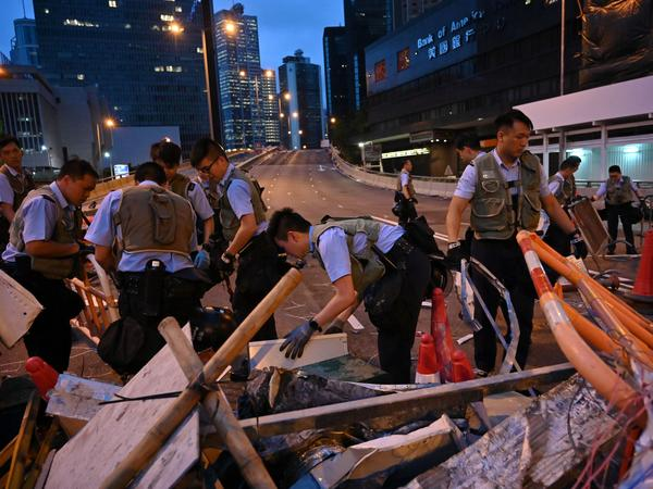 Police officers on Thursday dismantle barricades placed earlier by demonstrators in Hong Kong.