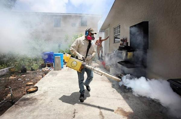 Miami-Dade County mosquito control inspector Carlos Varas sprays a Wynwood neighborhood.