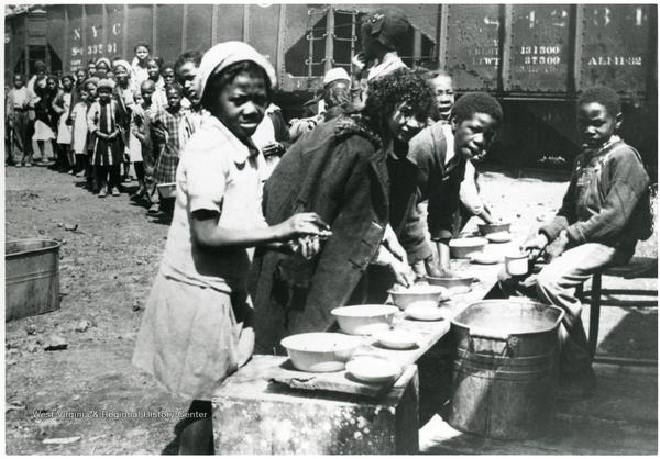 """Scott's Run miner's children lined up for a meal in the 1930s. In reaction to this photo Scotts Run elders said, """"There was a soup line or the blacks and there was a soup line for the whites, and that certainly proves it, how sad."""""""