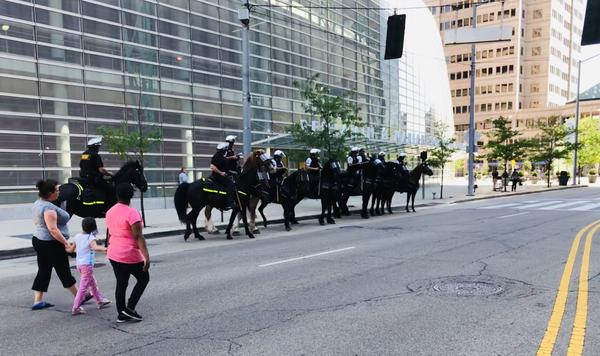 Police on horseback line up in front of the Schuster Center ahead of KKK-afiliated rally on Dayton 's Courthouse Square