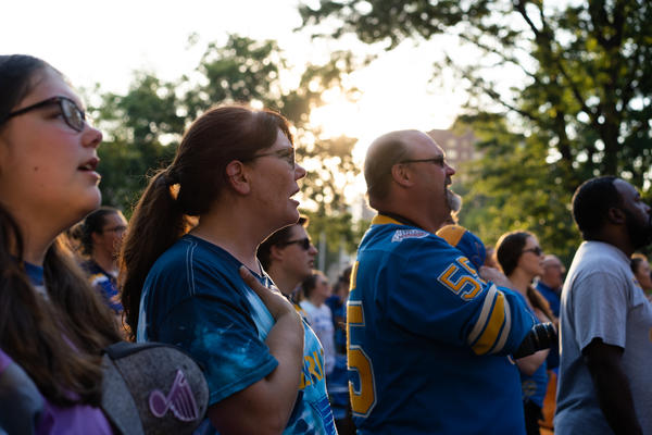 Blues fans sing the National Anthem in Eternal Flame Park on Sunday at a Game 6 watch party.