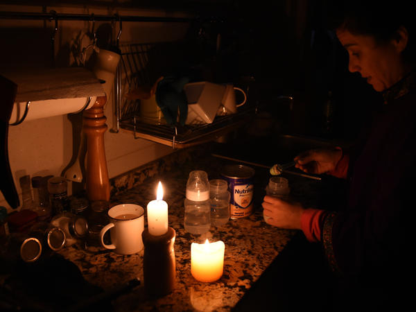 A woman prepares milk bottles Sunday using candles at her home in Montevideo during a power cut.