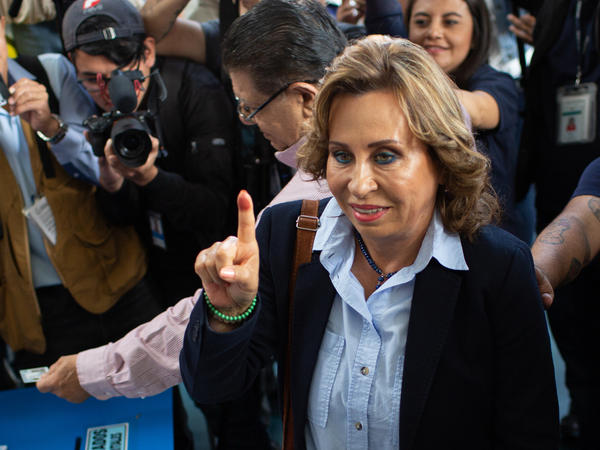 Sandra Torres, former first lady and presidential candidate for the National Unity of Hope (Union Nacional de la Esperanza) party (center), displays an inked finger after voting during presidential elections in Guatemala City on Sunday.