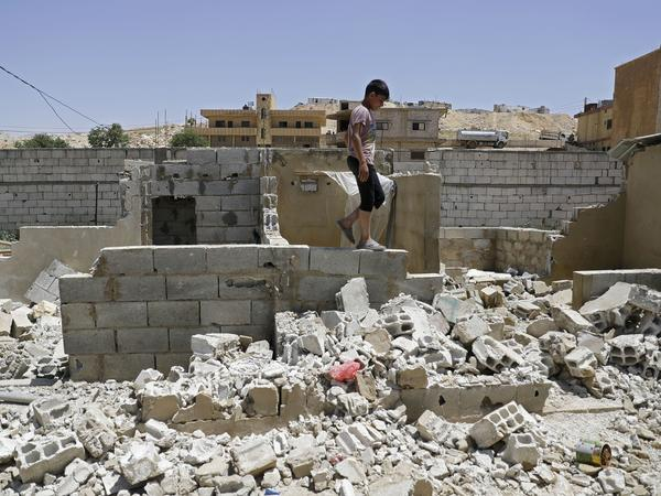 A Syrian boy walks among demolished shelters at a refugee camp in the northeastern Lebanese town of Arsal, in Lebanon's Bekaa valley, on June 10.