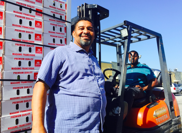 LET'S DO BUSINESS WITH HAITIAN FARMERS: Haitian-American importer Yvans Morisseau (left) with business partner Maly Sebastien Paul (right) unloading Haitian mangoes at their Horizon Vert warehouse in Miami Gardens.