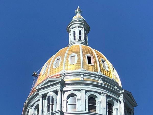 A worker cleans the gold dome of Colorado's state Capitol in June.