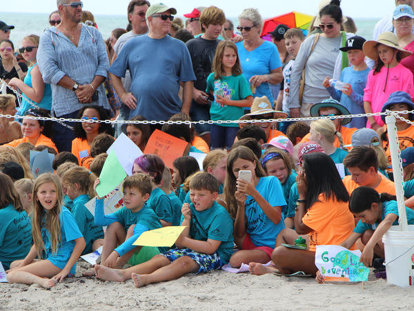 """Summer campers at the Loggerhead Marinelife Center wait to see a loggerhead turtle released, waving signs that say """"Welcome Home!"""" and """"Good Luck Bovenizer"""""""