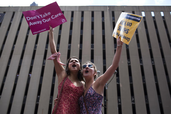 Juliana Hertel and Grace Hardison demonstrate against abortion restrictions during a Planned Parenthood rally in downtown St. Louis on Thursday.