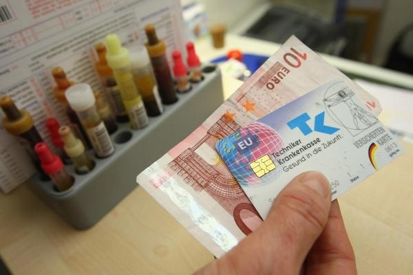 A secretary accepts 10 euros and a public health insurance card in Berlin, Germany. (Sean Gallup/Getty Images)