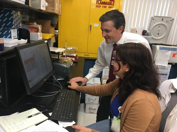 Researchers Patrick McGann and Anu Marahatta use pharmacology software and several drops of patients' blood to personalize the dosage of a sickle cell drug.