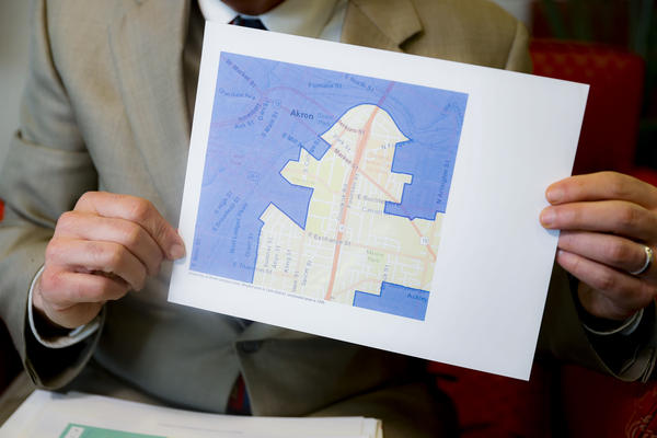 David Niven, a professor of political science at the University of Cincinnati holds a map demonstrating a gerrymandered Ohio district, Thursday, April 11, 2019, in Cincinnati.