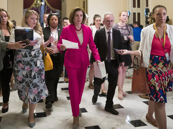 "Speaker Nancy Pelosi of California walks to the House floor Thursday. In a letter to Democratic lawmakers she announced the House would ""reluctantly"" pass a Senate version of an emergency immigration aid package."