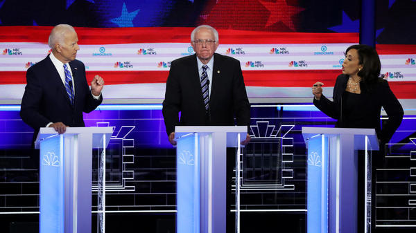 Former Vice President Joe Biden and  Sen. Kamala Harris of California exchange words about his record on racial justice Thursday during the second night of the first Democratic presidential primary debate. They flank Sen. Bernie Sanders.
