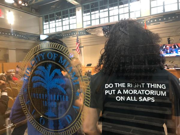 Protesters stand inside the Miami City Commission chambers during the Magic City final hearing late Thursday wearing a shirt advocating against the Magic City Special Area Plan (SAP).