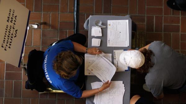 A Fannie Mae/Freddie Mac mortgage services representative (left) helps a person register for mortgage help in Miami.
