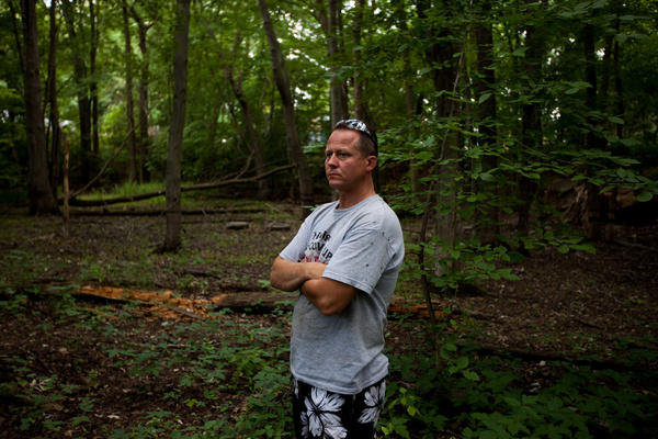 John Bolenbaugh stands in a forested stretch of the Kalamazoo River that borders a mobile home community in Battle Creek, Mich.