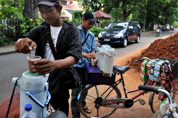 """An Indonesian """"Starbikes"""" vendor prepares coffee from his bicycle for street laborers in Jakarta."""