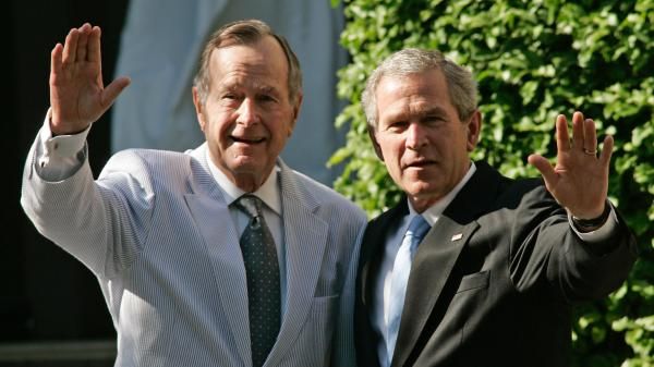 Former President George W. Bush (right) and his father, former President George H.W. Bush, wave as they leave a family wedding in Washington, D.C., in May 2006.