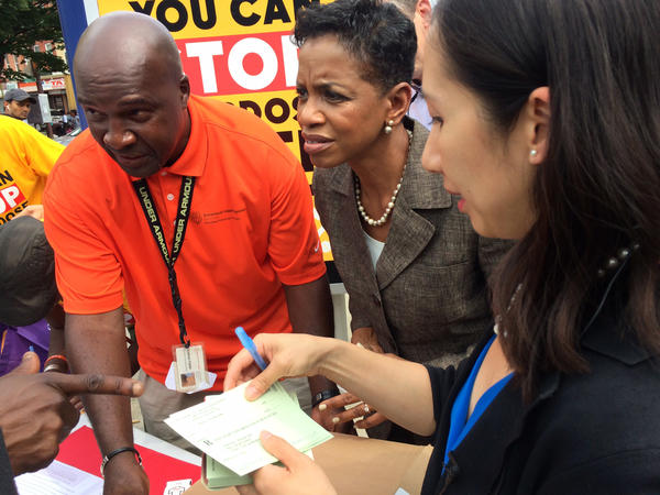 Health worker Nathan Fields (left), Rep. Donna Edwards and Dr. Leana Wen show people how to use naloxone on a street corner in Sandtown, a Baltimore neighborhood where drug activity is common.