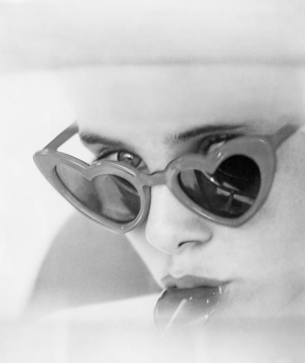 """Actress Sue Lyon eats a lollipop as Dolores """"Lolita"""" Haze in a scene from <em>Lolita</em>, the 1962 film adaptation of Vladimir Nabokov's novel. Nabokov made sumptuous use of food in his writing, and the acoustic affinity between Lolita and lollipops is no coincidence."""