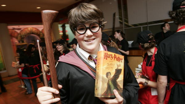 A fan holds a copy of <em>Harry Potter and the Deathly Hallows</em> at a book release party at Scholastic headquarters in New York in 2007.