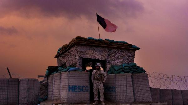 A U.S. Marine from the 1st Battalion, 8th Marines, Alpha Company looks out as an evening storm gathers above an outpost near Kunjak, in southern Afghanistan's Helmand province.