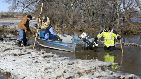 Tom Wilke, his son Chad, and Nick Kenny launch a boat into the swollen waters of the Elkhorn River to check on Wilke's flooded property, in Norfolk, Neb., on Friday, March 15.