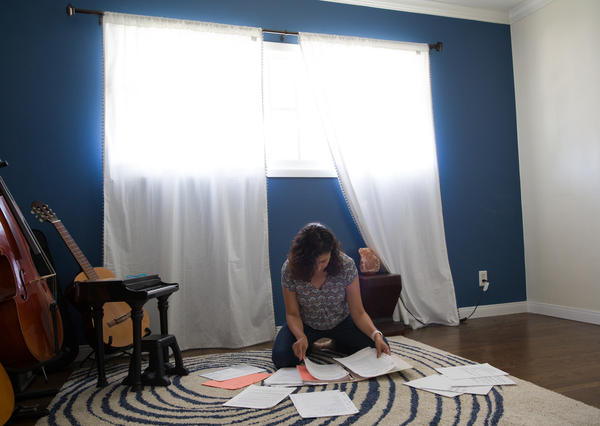 Jeannine sorts through a binder of writing assignments from her therapy. In keeping a journal about her past experiences with pain, she noticed that the pain symptoms began when she was around 8 — a time of escalating family trauma at home.