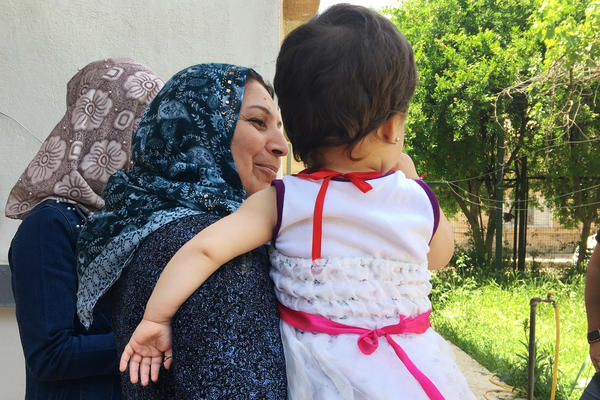 Caregiver Fajriya Khaled holds a child at an orphanage in northeastern Syria, home to 41 children of Yazidi mothers and ISIS fathers. The Yazidi community in Iraq forces the women to leave their children behind if they want to return home.