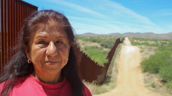 Maria Ochoa poses by the Arizona-Mexico border wall, south of Tucson, Ariz.