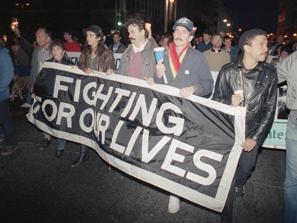 Marchers at a candlelight vigil in San Francisco, Calif., carry a banner to call attention to the continuing battle against AIDS on May 29, 1989. The city was home to the nation's first AIDS special care unit. The unit, which opened in 1983, is the subject the documentary <em>5B.</em>