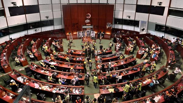 Protesters flooded into Hong Kong's parliament chamber after breaking into the government's headquarters on Monday — the 22nd anniversary of the city's handover from Britain to China.