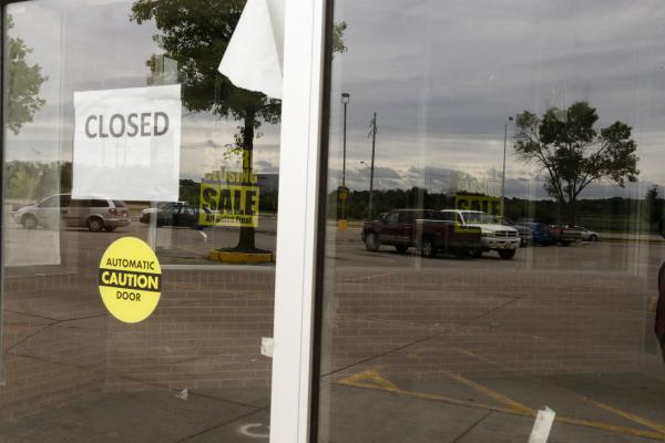 "In this Aug. 26, 2016 photo, a parking lot is reflected in the windows of a closed Hy-Vee store in Lincoln, Neb. The neighborhood is now considered a ""food desert."""