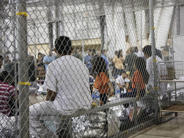 Migrants taken into custody related to cases of illegal entry into the United States sit in a facility in McAllen, Texas, in June 2018. On Tuesday, a federal judge ruled that asylum-seeking migrants can't be denied bond and held indefinitely.