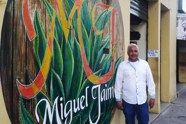 """Jaime Vásquez, a well-known cocuy maker and one of the country's most enthusiastic ambassadors for the liquor, stands in front of his cocuy store. """"We are very proud of this drink,"""" he says. But for decades, cocuy was illegal and production went underground. """"A lot of people went to prison for selling cocuy,"""" Vásquez says. Cocuy producers """"were treated like drug traffickers."""""""