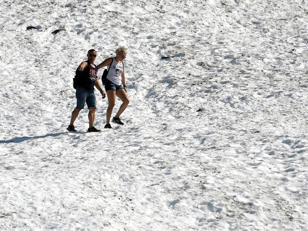 People hike on the Byron Glacier on Thursday in Girdwood, Alaska, southeast of Anchorage. Many cities set heat records amid unusually hot and dry conditions in the area.