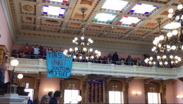 """Protestors unfurl sign as House approves """"Heartbeat Bill"""""""