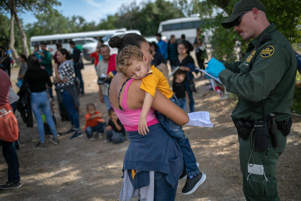 A U.S. Border Patrol agent takes down personal data from Salvadorian mother Ana Esmeralda and her son Manuel Alexander, 2, after they were taken into custody on July 2 in Los Ebanos, Texas.