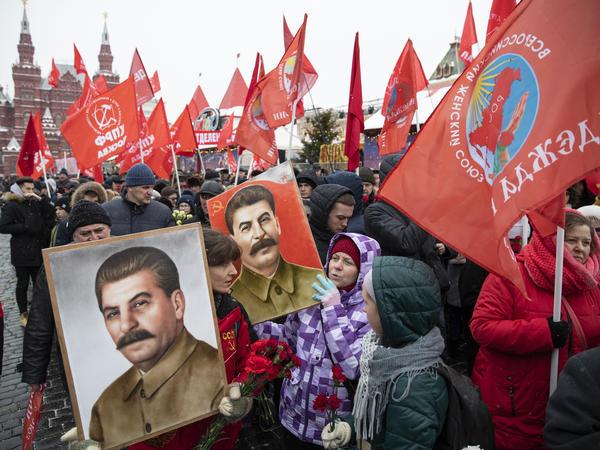 People hold portraits of Soviet leader Josef Stalin in December 2018 as they line up in Moscow to lay flowers at his grave.