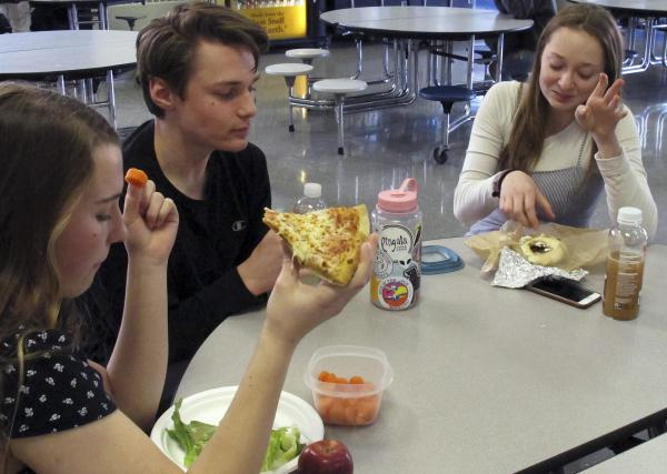 In this Friday, April 5, 2019 photo, Burlington High School student Emma McCobb, left, holds a piece of pizza while eating with classmates in the school cafeteria in Burlington, Vt.