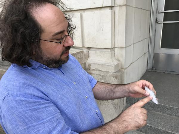 Anthony Rubano examines a piece of broken glass from one of the State Armory building's lighting fixtures in June 2019.