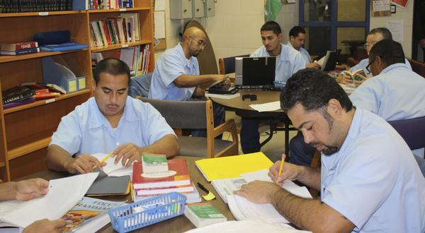 Incarcerated men working inside the Education Justice Project library at the Danville Correctional Center.