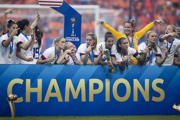 The U.S. Women's National Team celebrate with the trophy following victory in the 2019 FIFA Women's World Cup.