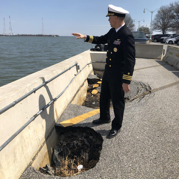 Commander David McKinney, a spokesman for the U.S. Naval Academy, stands alongside a sinkhole on the Severn River waterfront, where the Academy plans to build a new seawall to better withstand flooding.