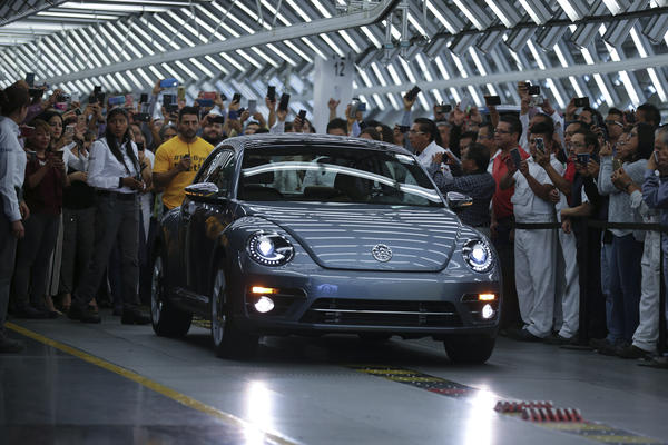 "Employees take photos of the Final Edition version of the Volkswagen Beetle, painted ""stonewash blue"" according to the company, as it rolls out at the production plant in Puebla, Mexico. The last Beetle is not for sale, but destined instead for a museum."