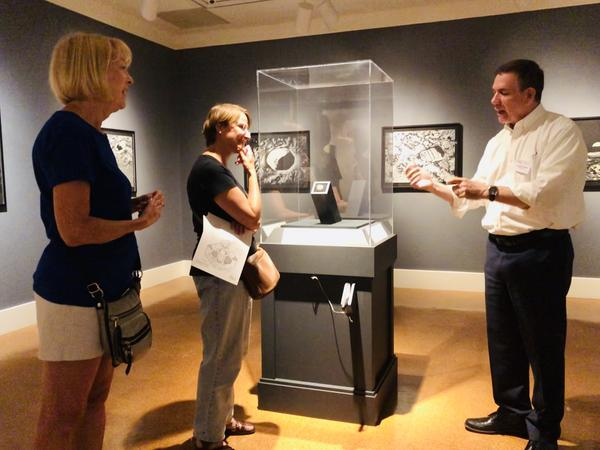 DAI Chief Curator, Dr. Jerry Smith, talks to museum visitors about The Moon Museum's history. Pictured are Karen Kind of Springboro (Left) and Laurie Mattern (Center), originally of Huber Heights now living in Germany.