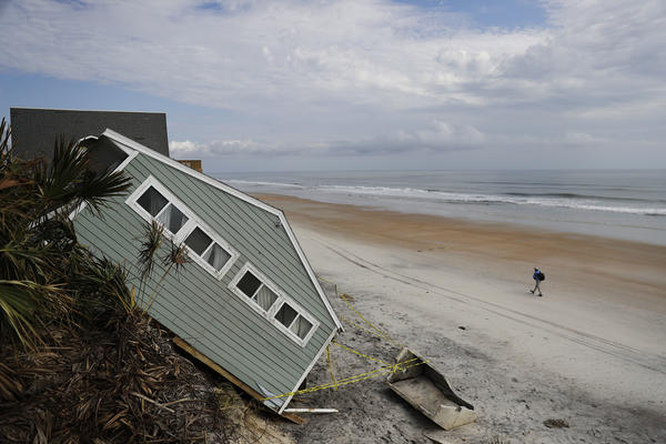 A house rests on the beach after collapsing off a cliff from Hurricane Irma in Vilano Beach, Fla.